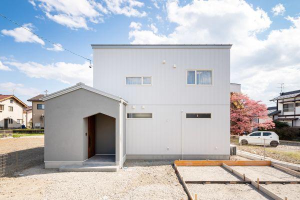 塗り壁と白ガルバリウムと三角屋根のかわいいお家   ココチエ一級建築士事務所